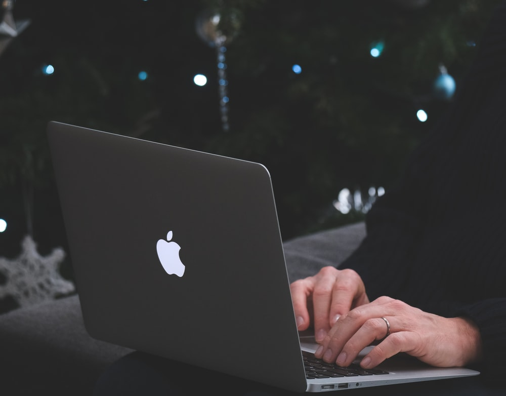 person using macbook air during nighttime