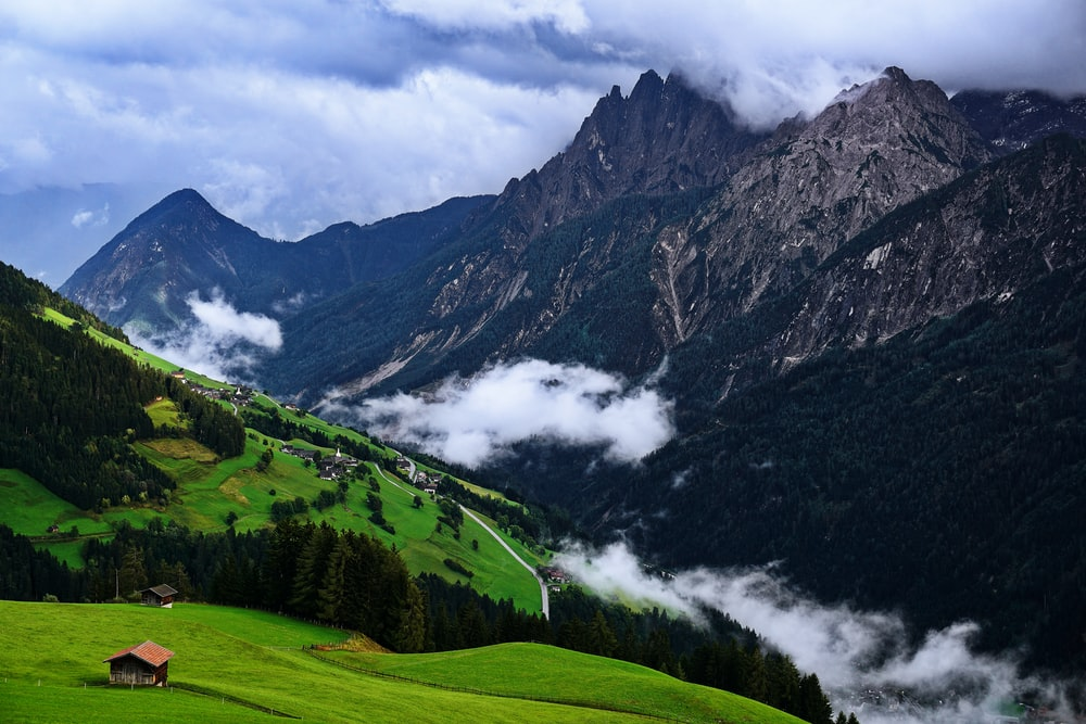 green grass field and mountains under white clouds and blue sky during daytime