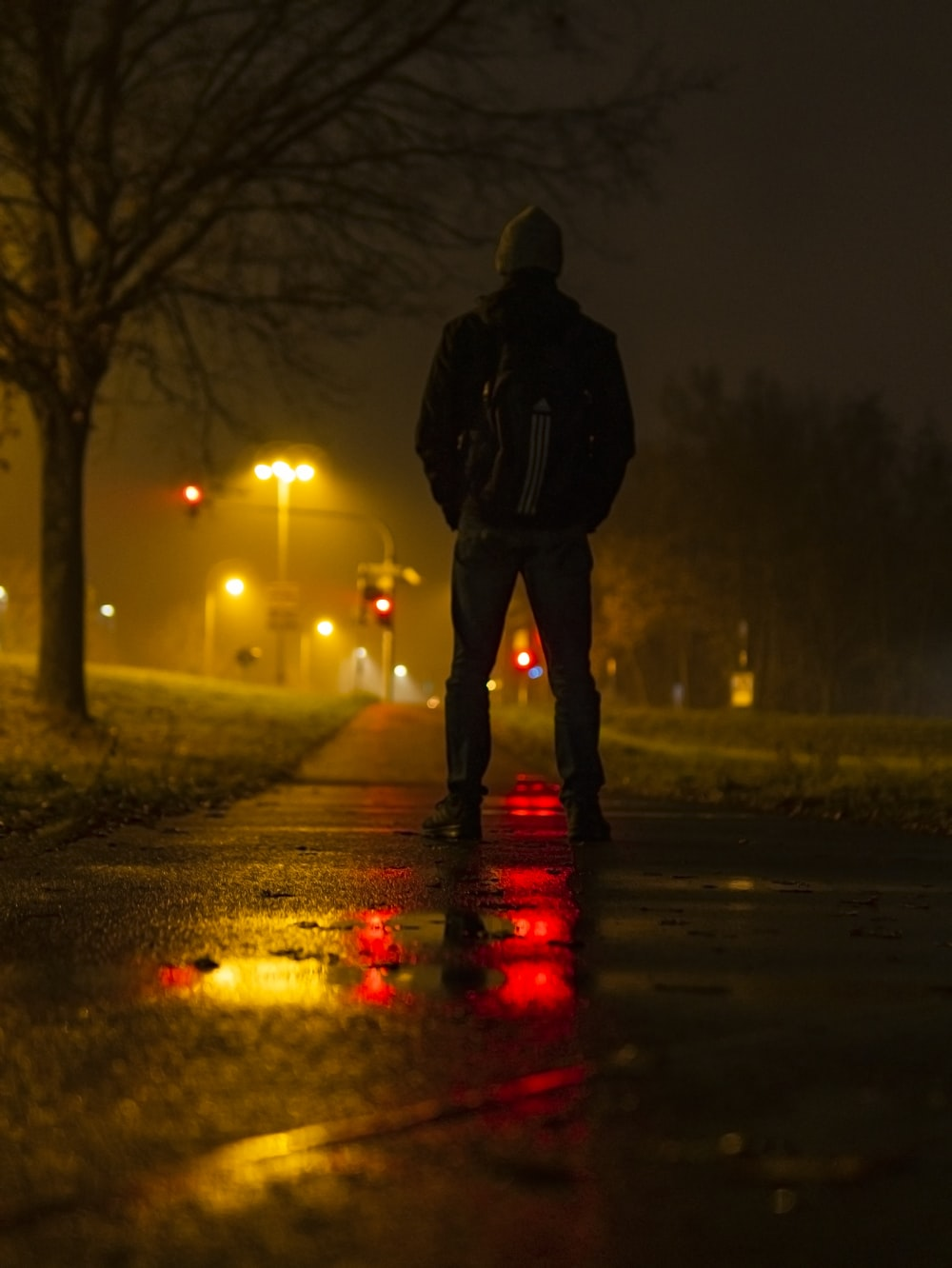 man in black jacket standing on road during night time