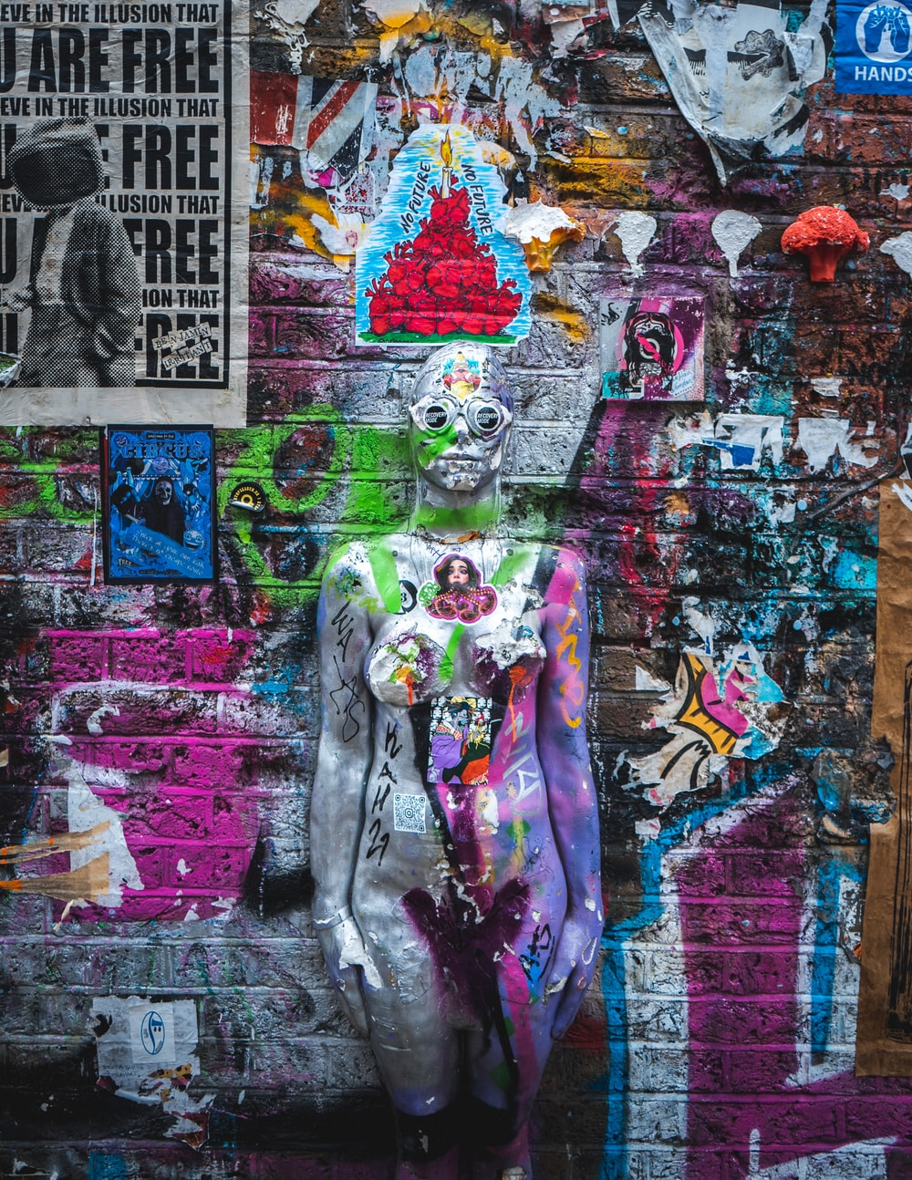 woman in gray jacket and purple pants standing beside graffiti wall