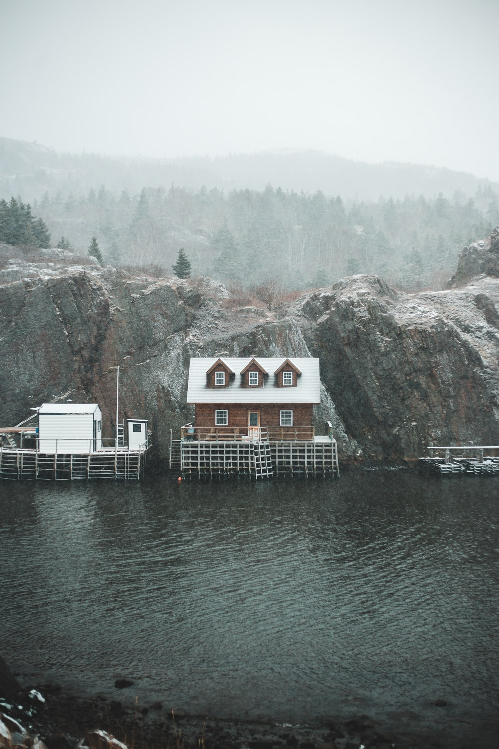 white and brown wooden house near body of water during daytime