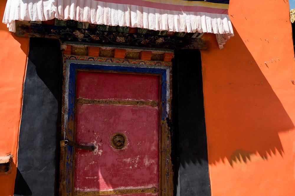 red wooden door with green door knob