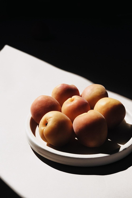 brown round fruit on white ceramic plate