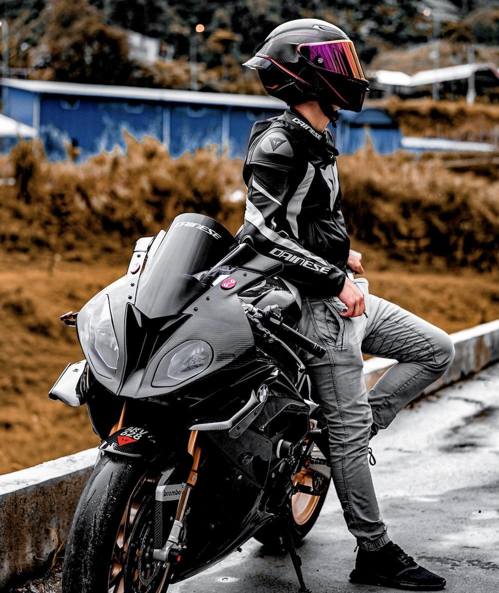 man in black leather jacket riding black motorcycle during daytime