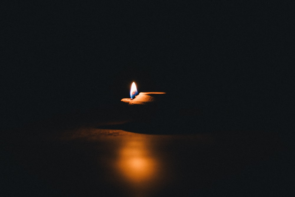 lighted candle on brown wooden table