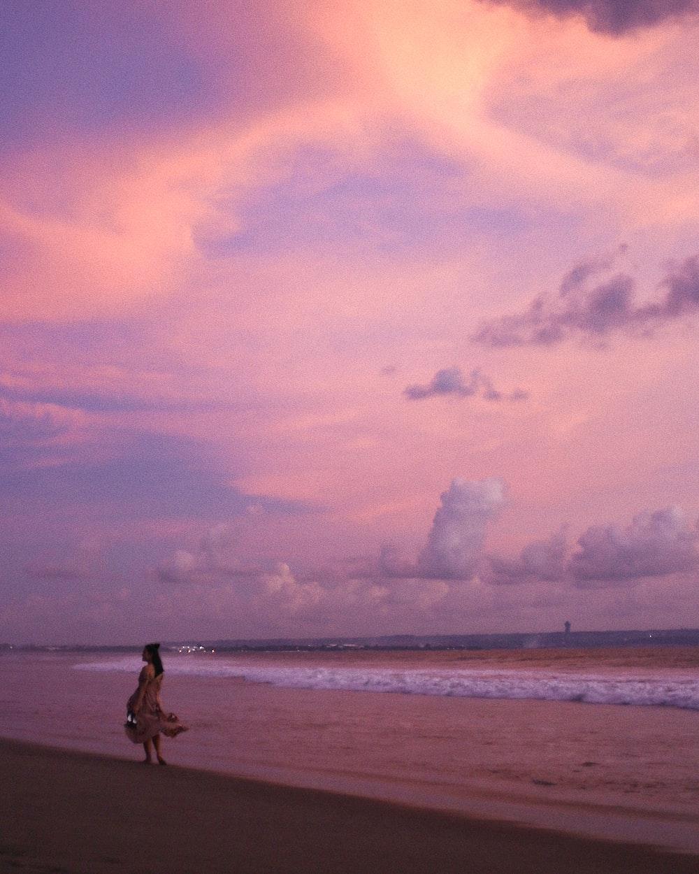 man in black shorts walking on beach during daytime