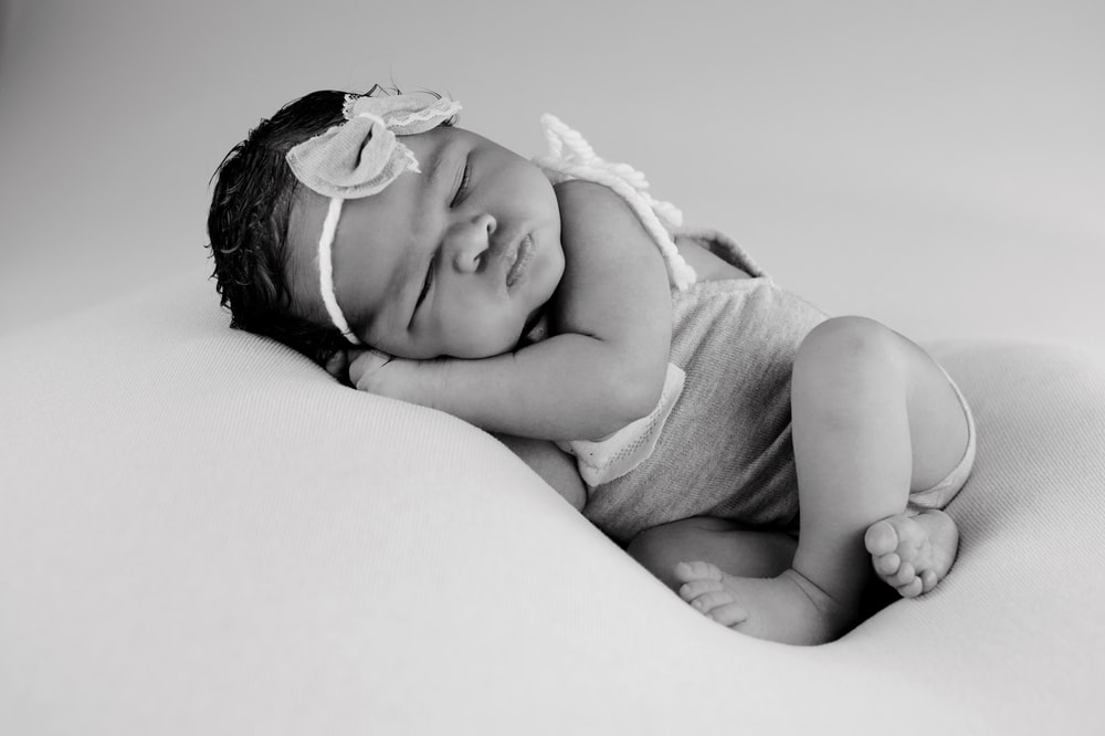 grayscale photo of baby lying on bed