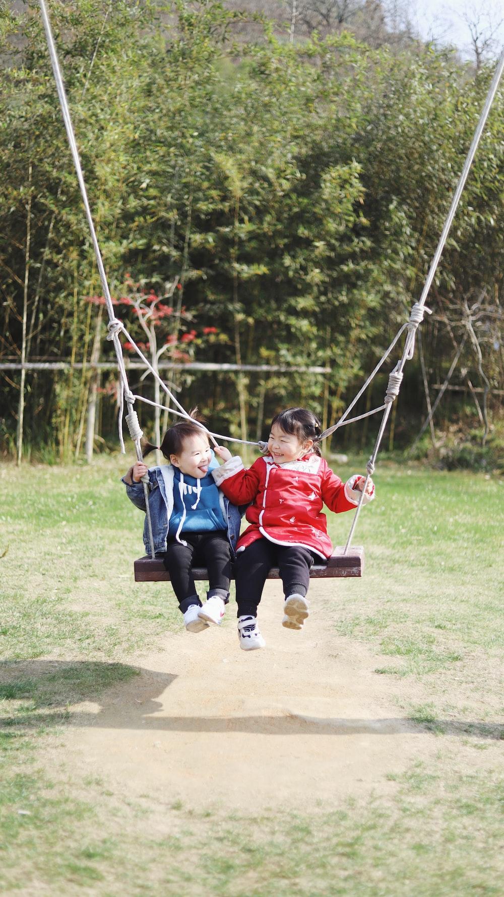 2 boys sitting on swing during daytime