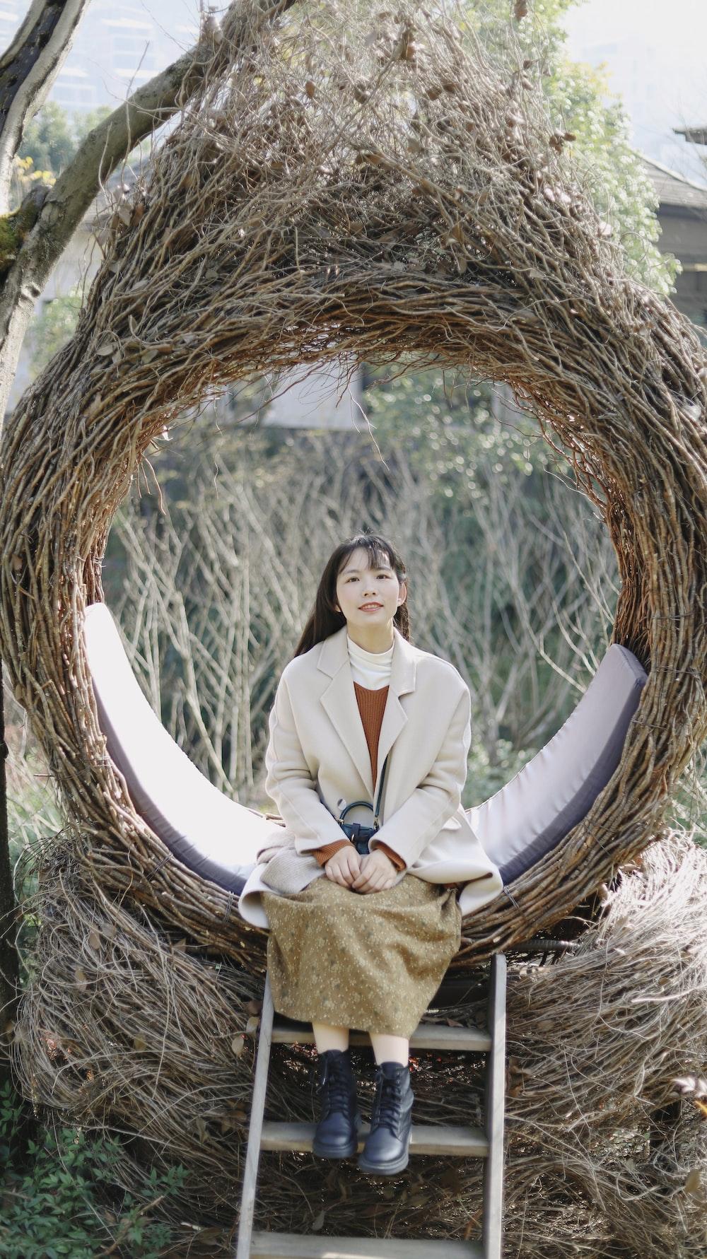 woman in white blazer and brown skirt sitting on brown round nest