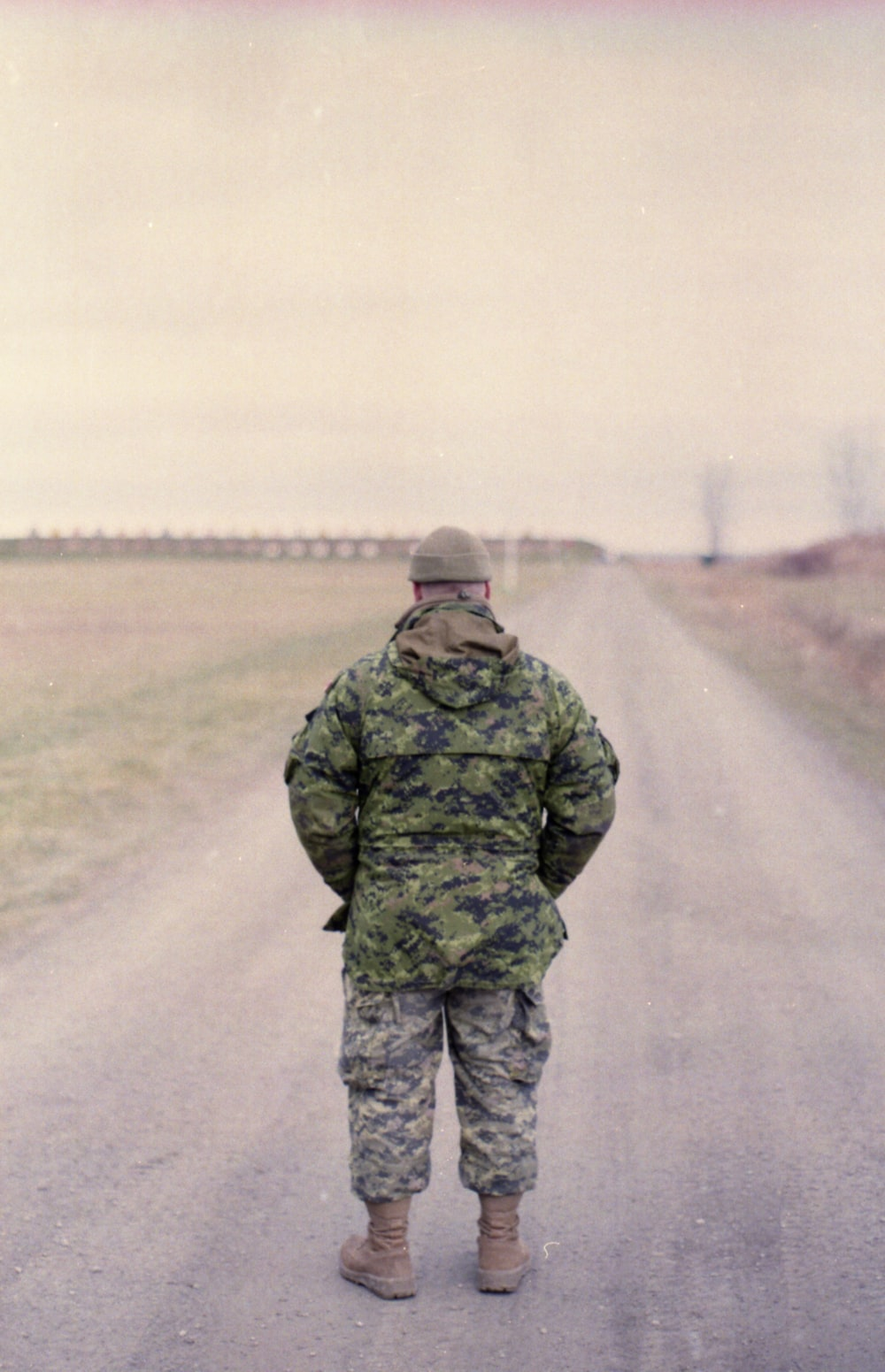 man in green camouflage uniform standing on road during daytime