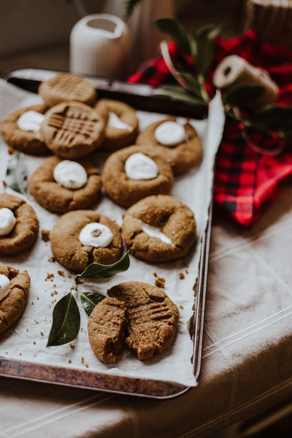 cookies on white paper beside red and white checkered textile