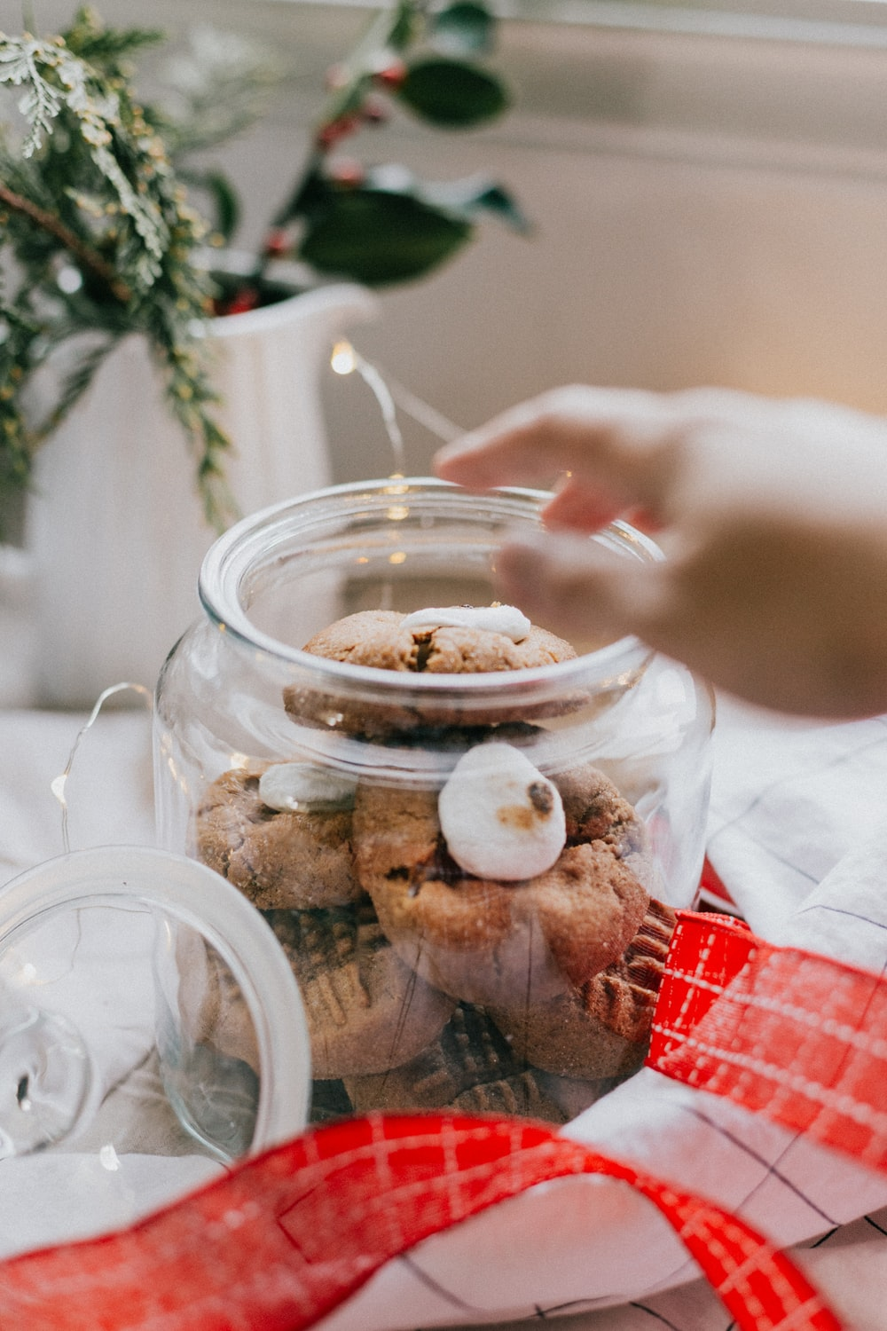 person holding clear glass jar with food
