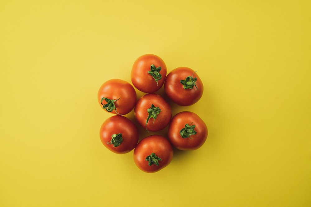 red tomato on yellow surface