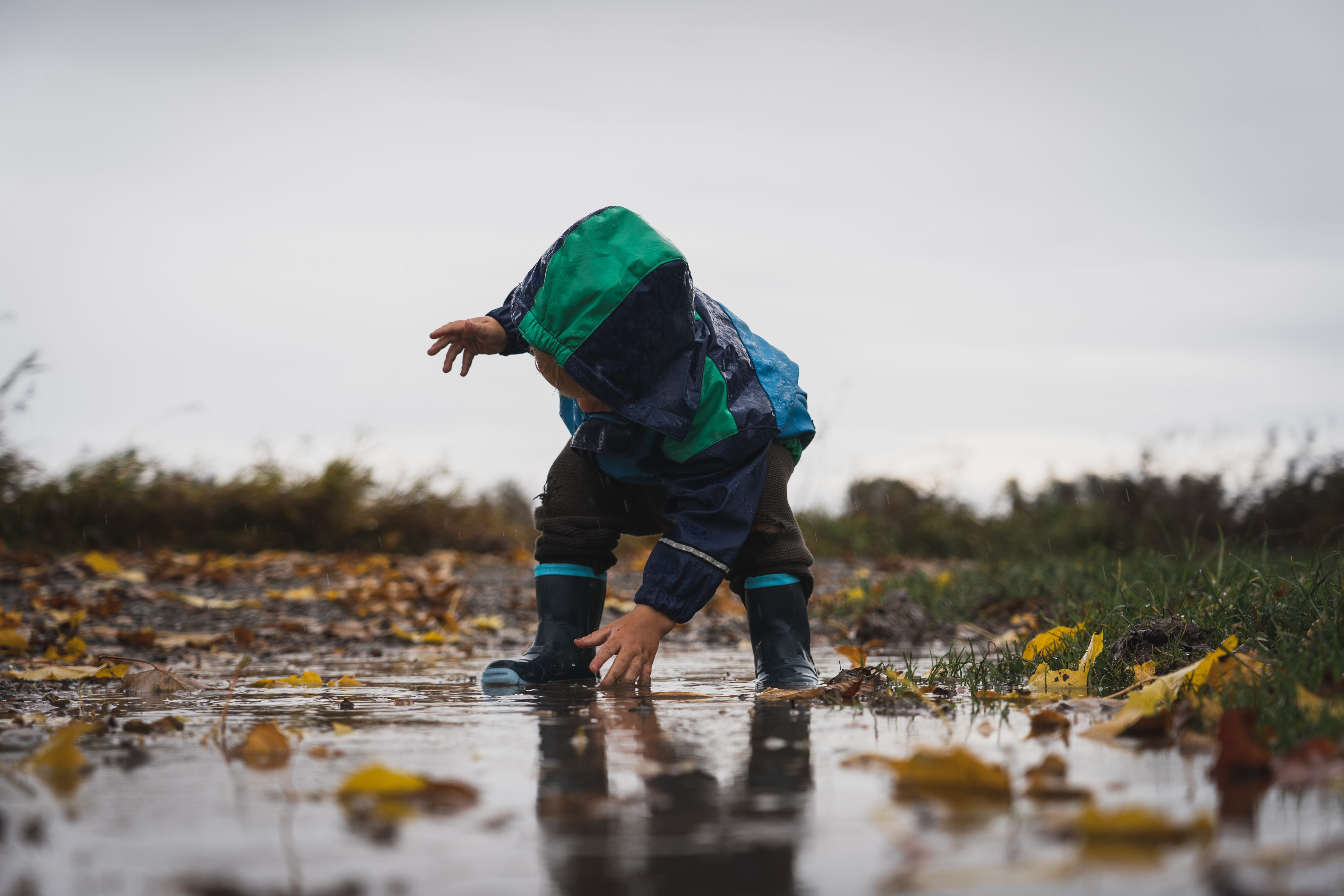 Cute little child playing in a puddle during rain
