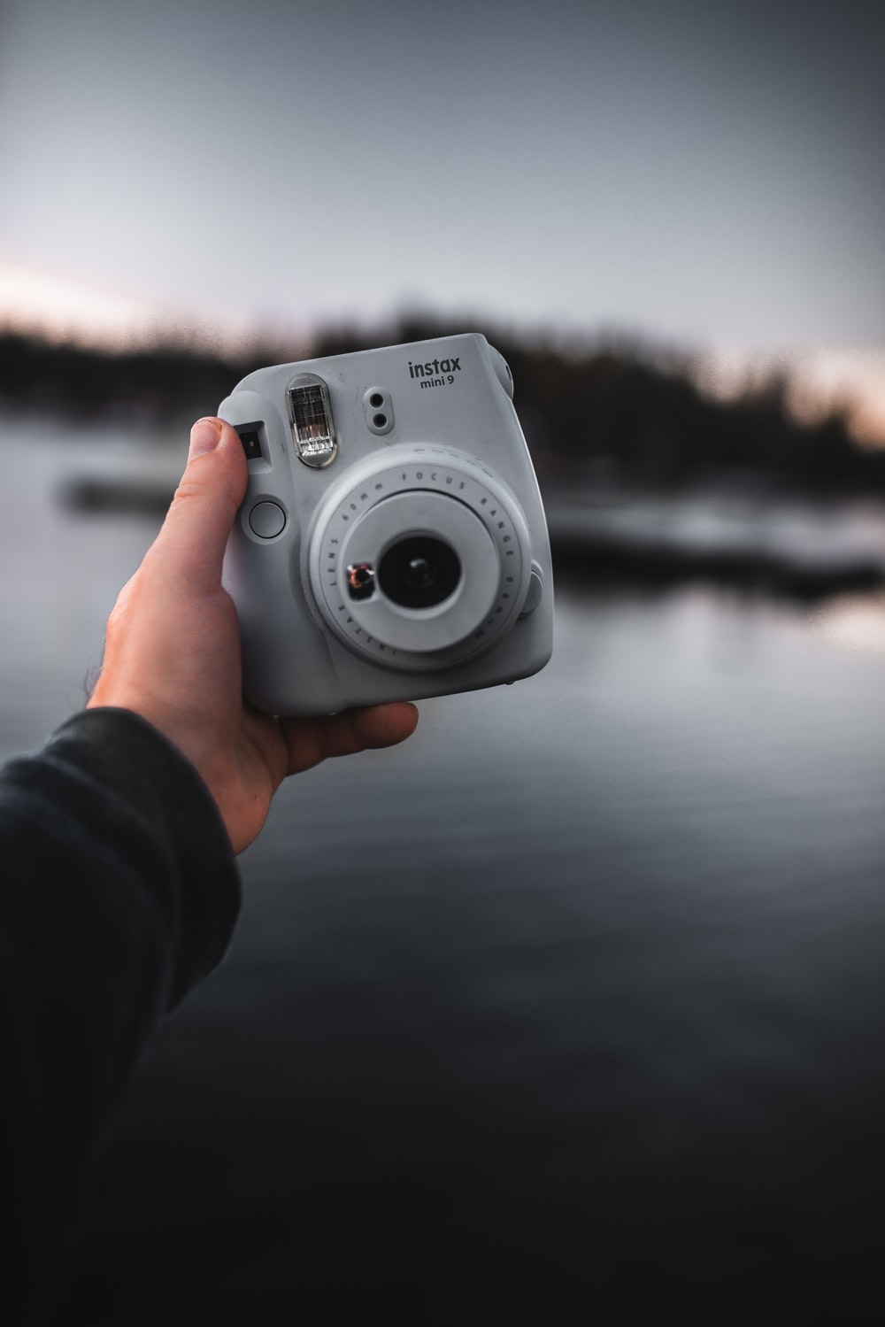 person holding gray and black camera