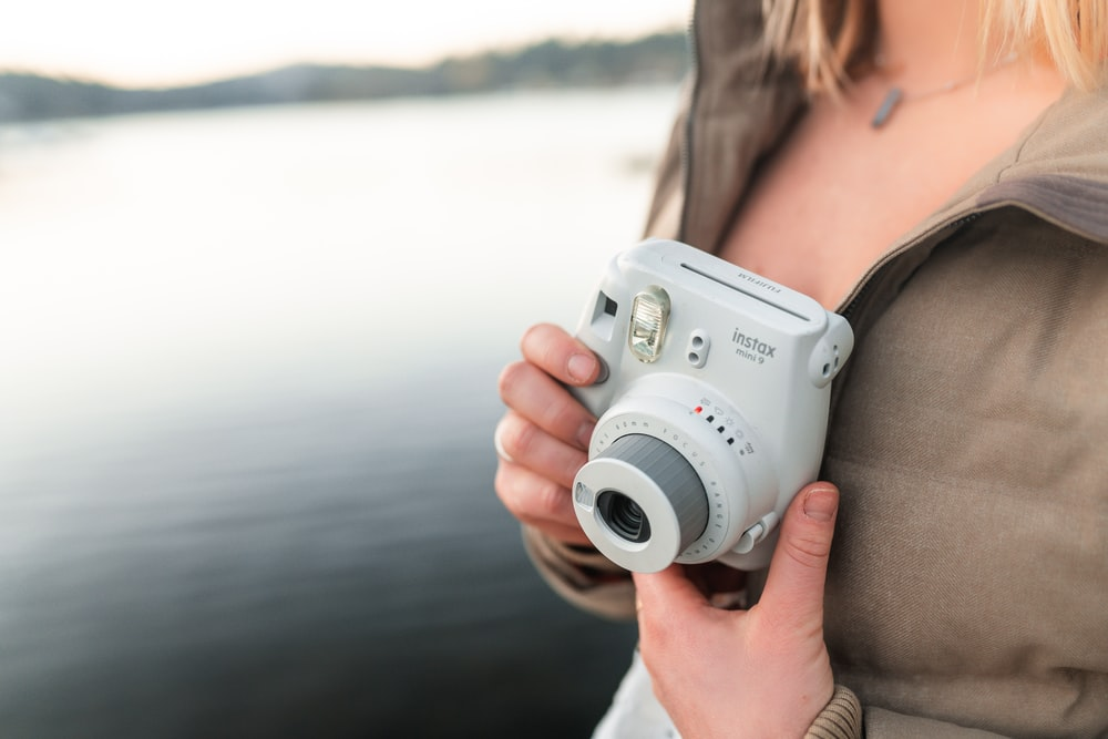woman holding white and gray camera