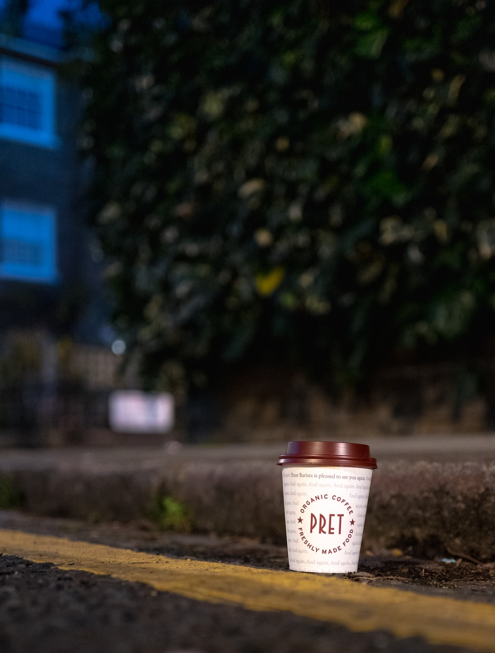 white and brown disposable cup on brown soil