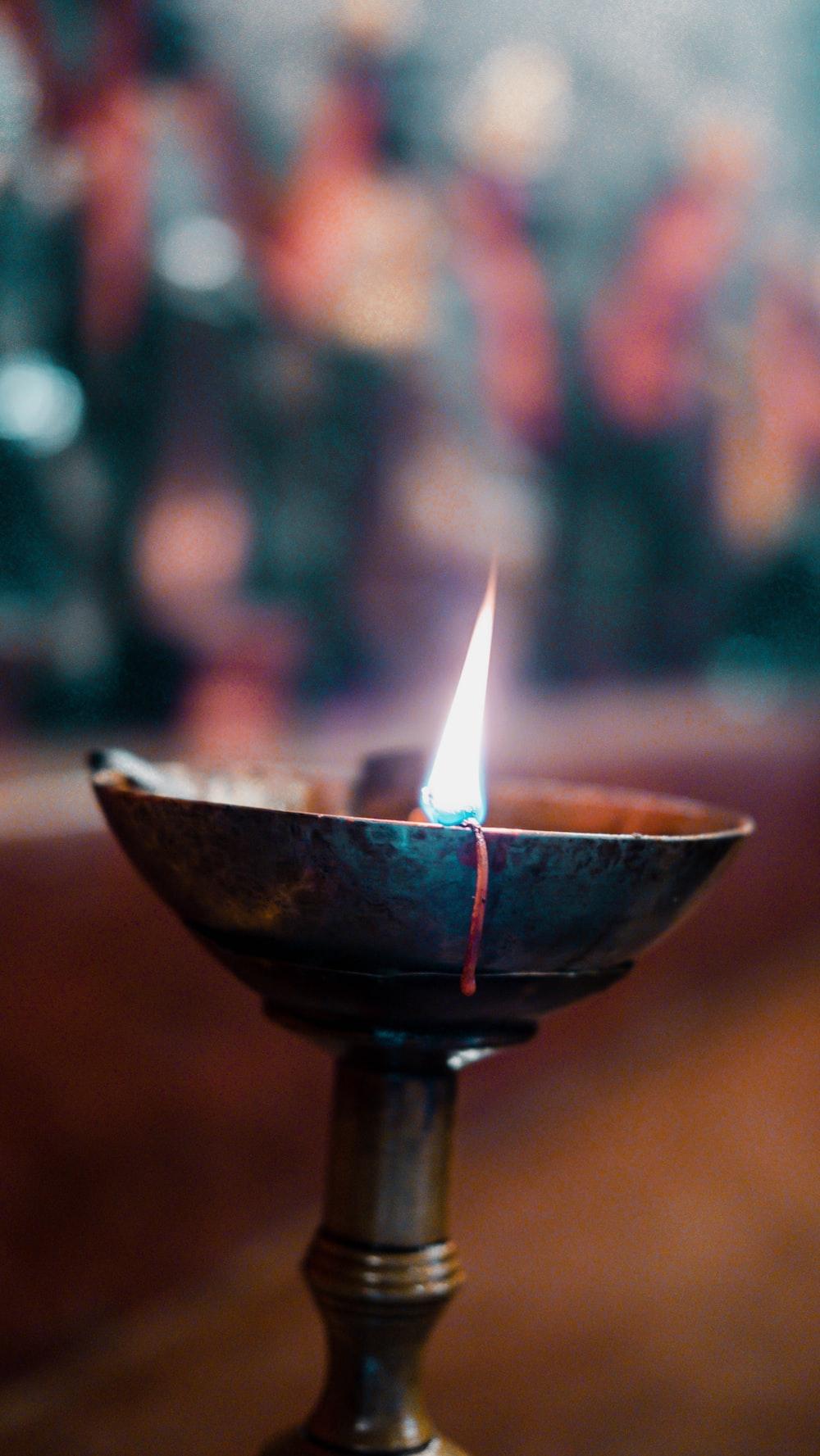 lighted candle on black ceramic candle holder