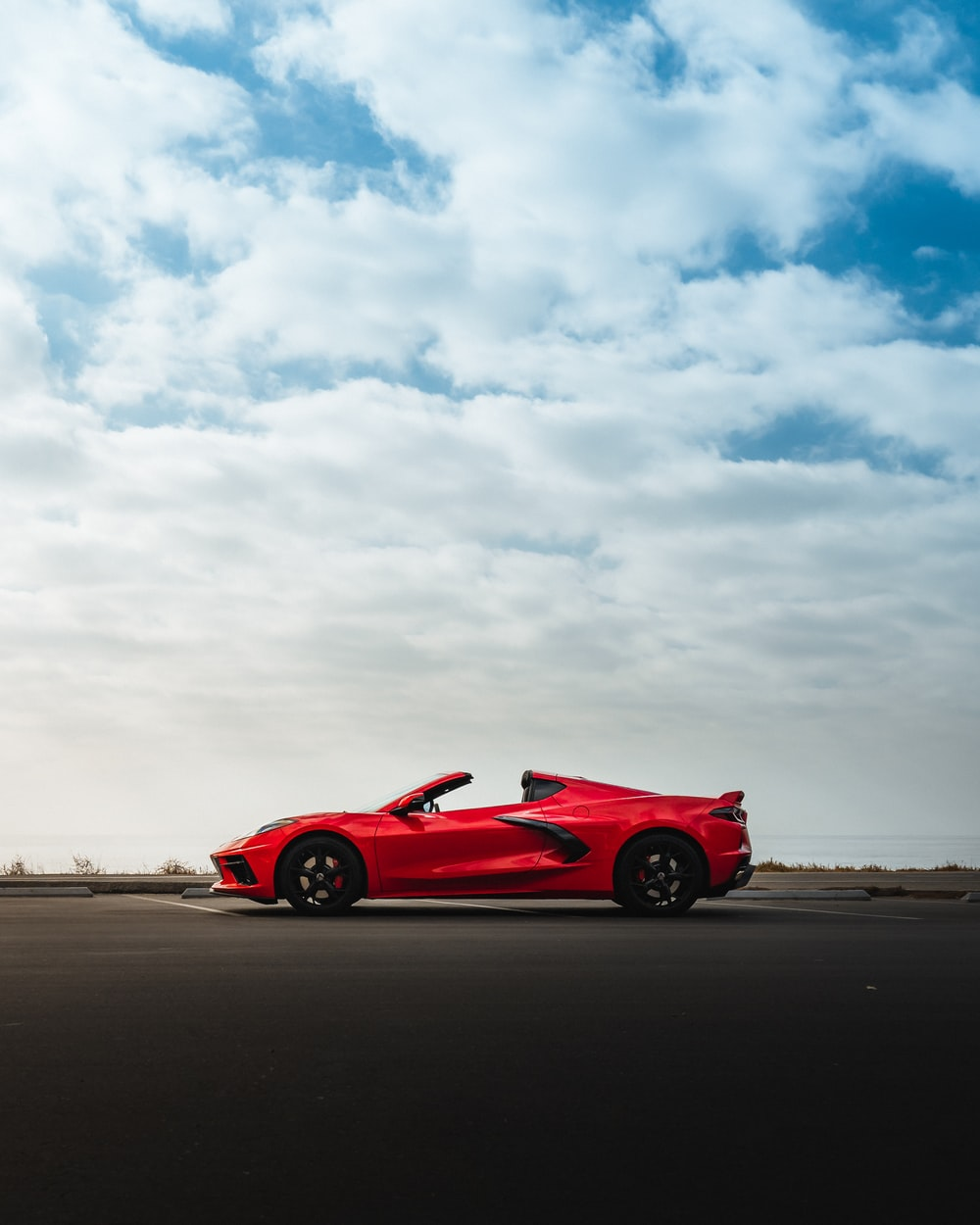 red ferrari 458 italia on brown sand under white clouds during daytime