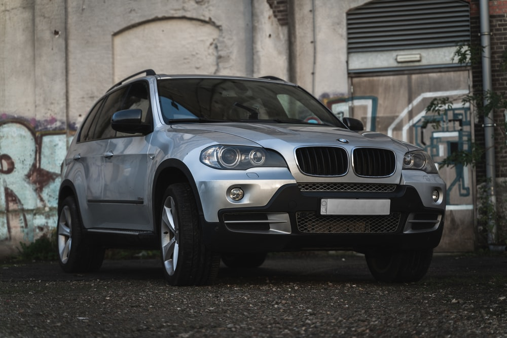 black bmw x 6 parked on gray concrete floor during daytime