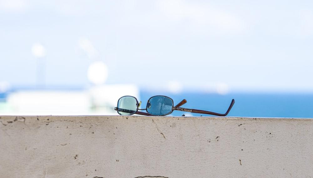 black framed sunglasses on brown wooden surface
