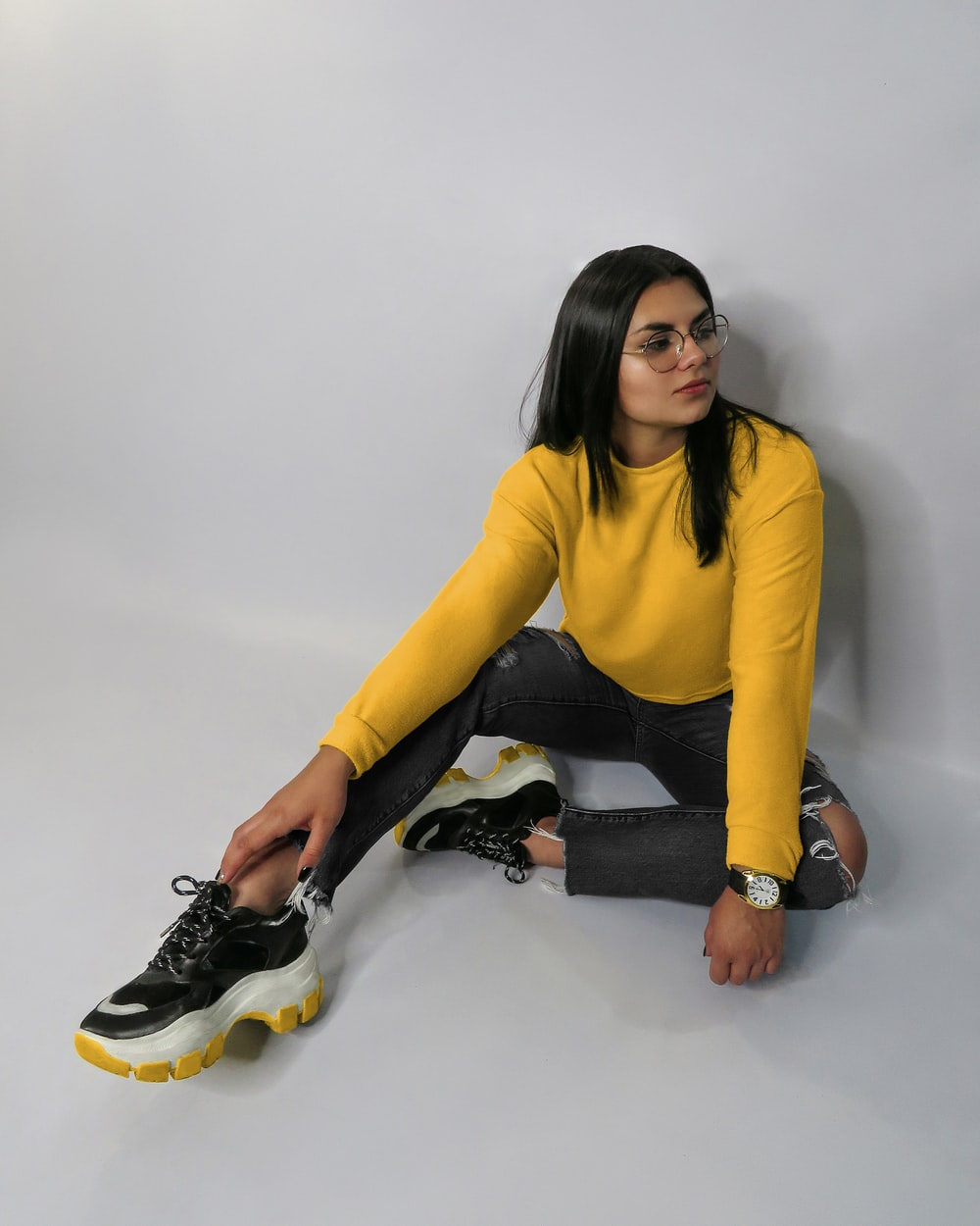 woman in yellow long sleeve shirt and black pants sitting on white floor