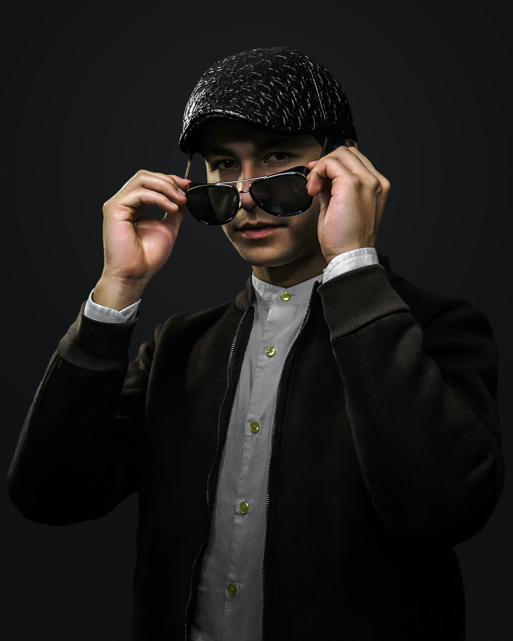 man in black coat wearing black knit cap and black sunglasses