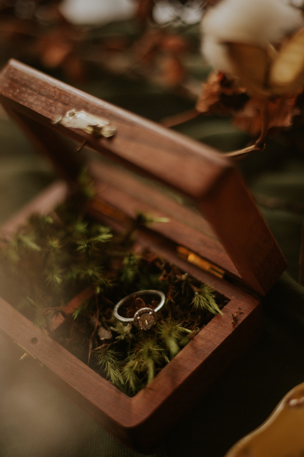 silver ring on brown wooden box