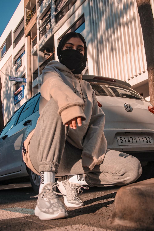 man in brown jacket and black helmet sitting on blue car