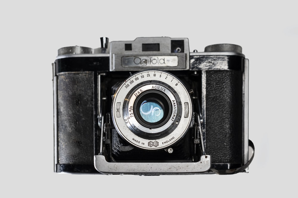 black and silver camera on white surface
