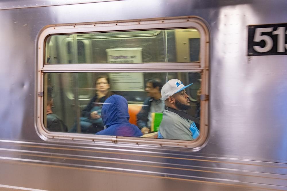 man in blue shirt sitting on train