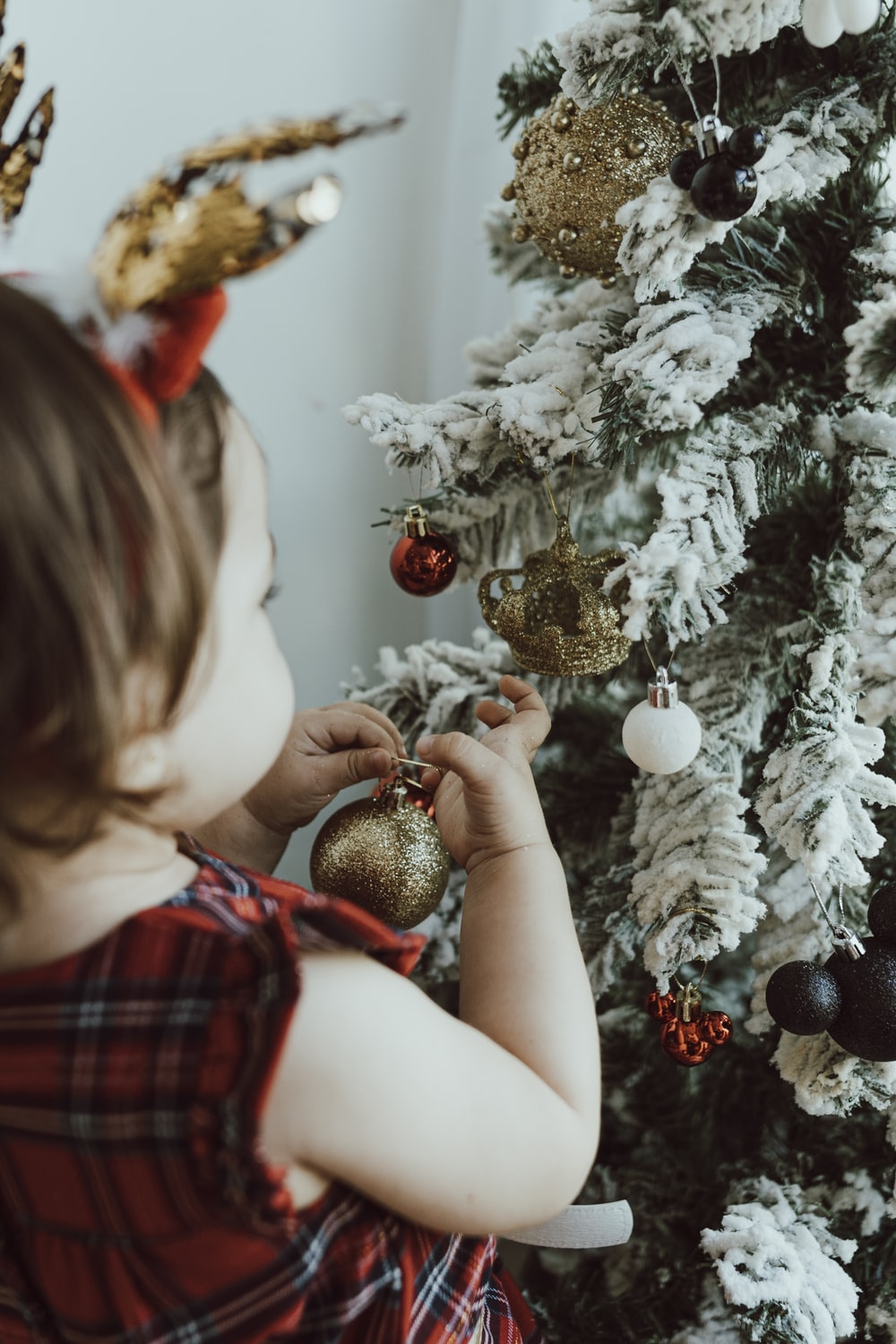 girl in red and white plaid dress holding gold and silver baubles