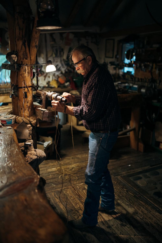 man in blue denim jeans holding brown wooden stick