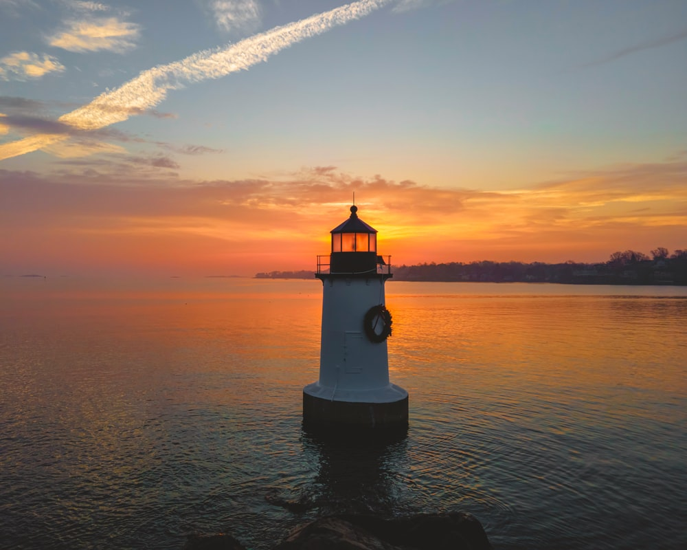 white and black lighthouse on body of water during sunset