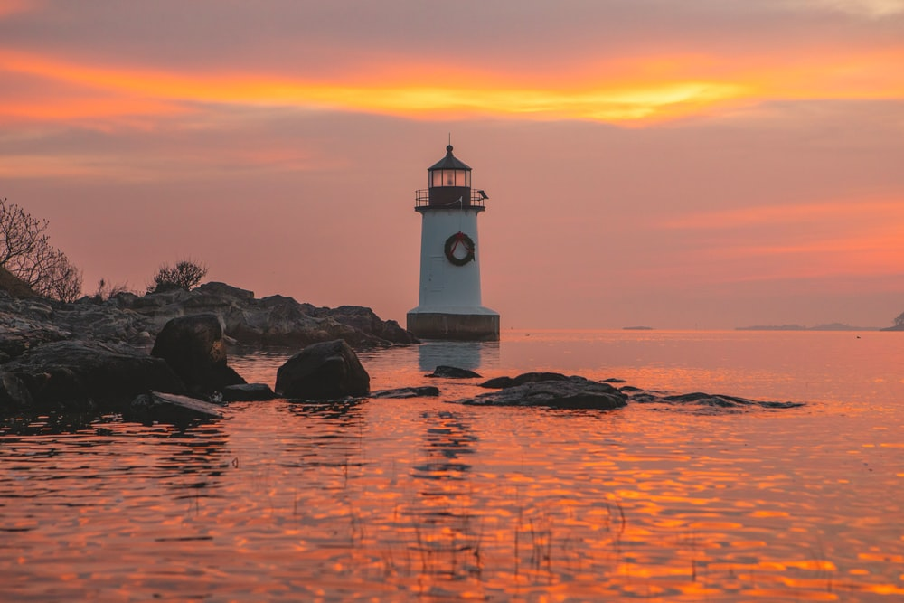 white lighthouse on rock formation on sea water during sunset