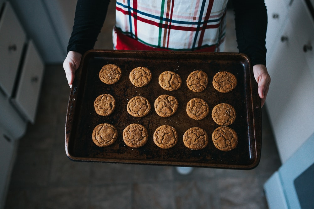 person holding tray of cookies