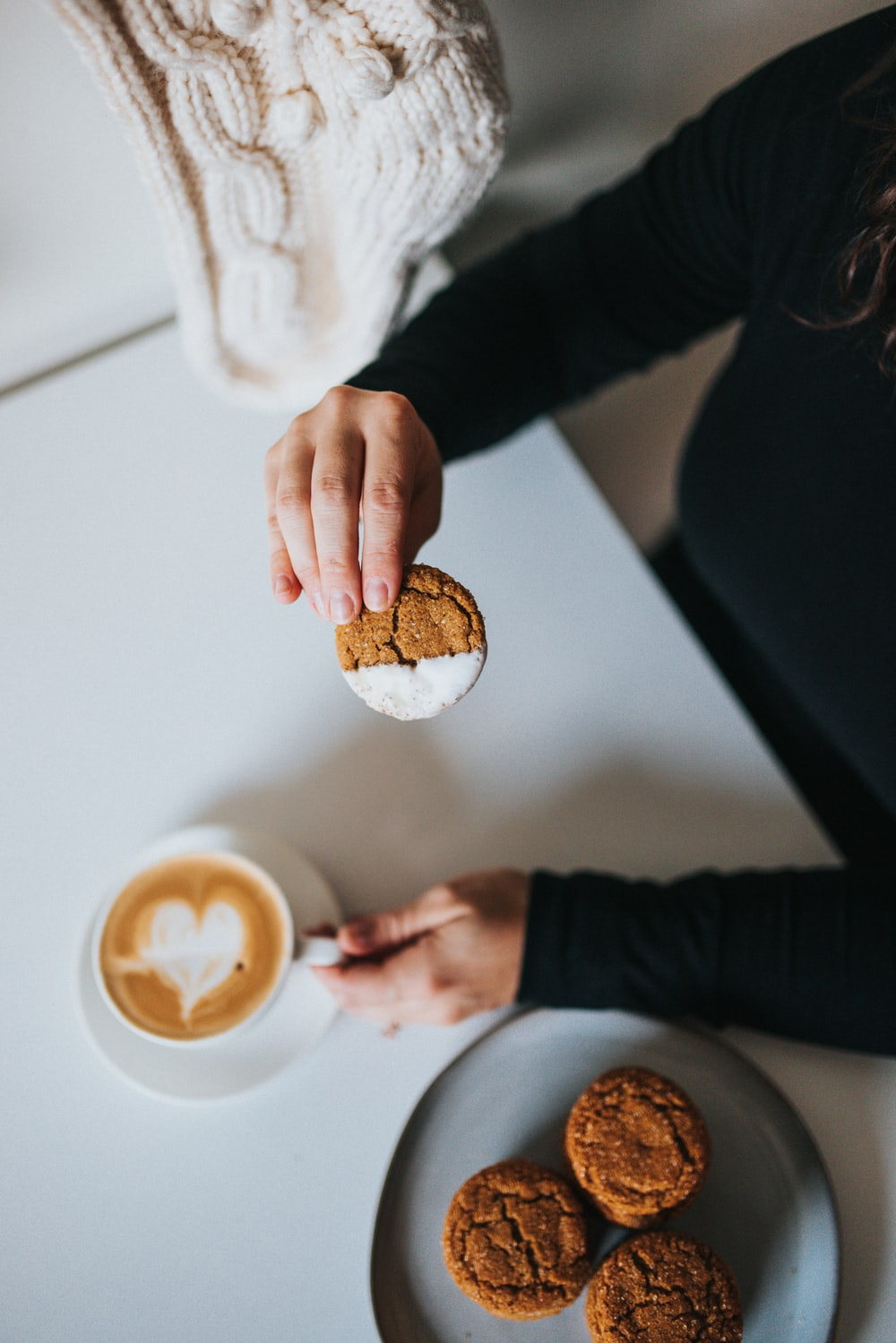 person holding brown bread near white ceramic mug with coffee