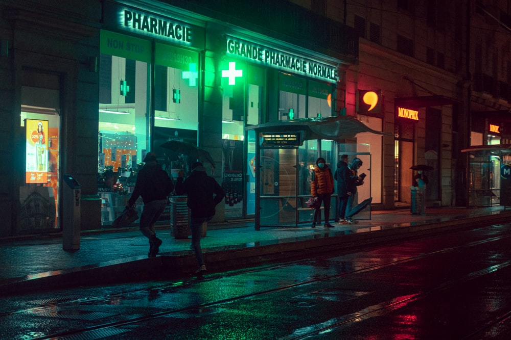 man and woman walking on sidewalk during night time