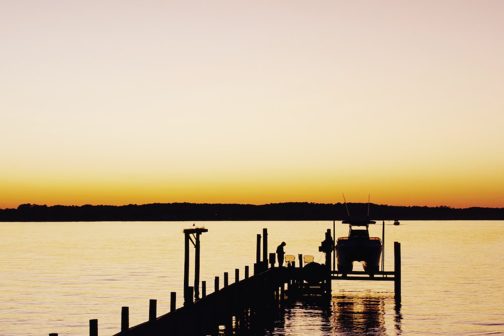silhouette of people on dock during sunset