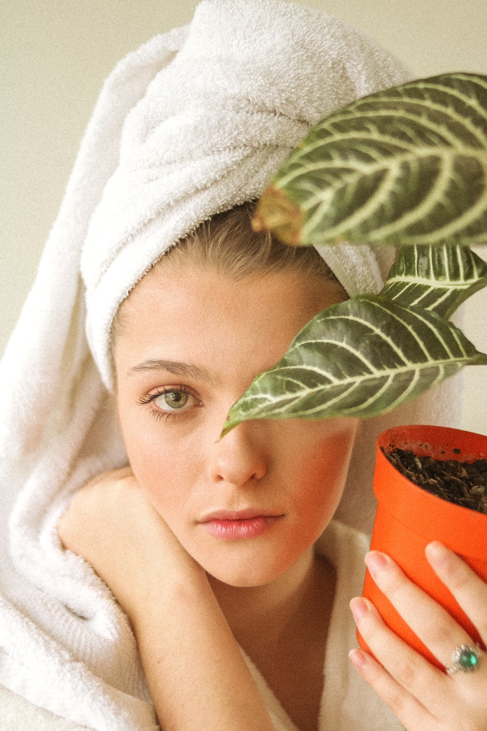 girl in white bath towel holding brown pot with green plant