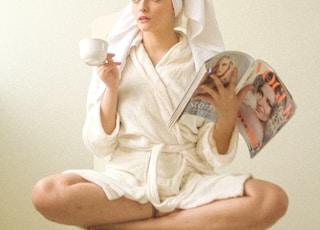 woman in white hijab holding white ceramic mug