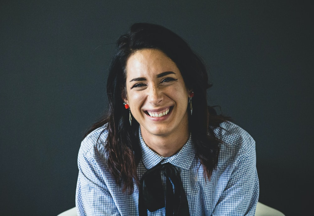 smiling woman in white and black checkered dress shirt