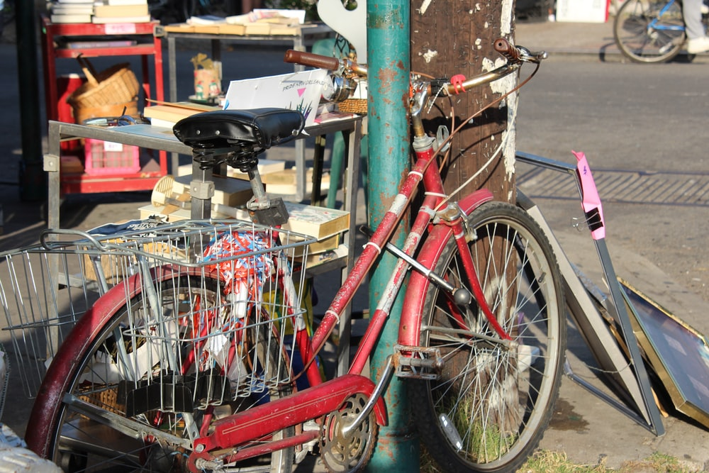 red city bike parked beside green post