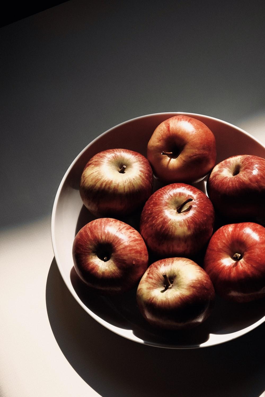 red apple fruit on white ceramic bowl