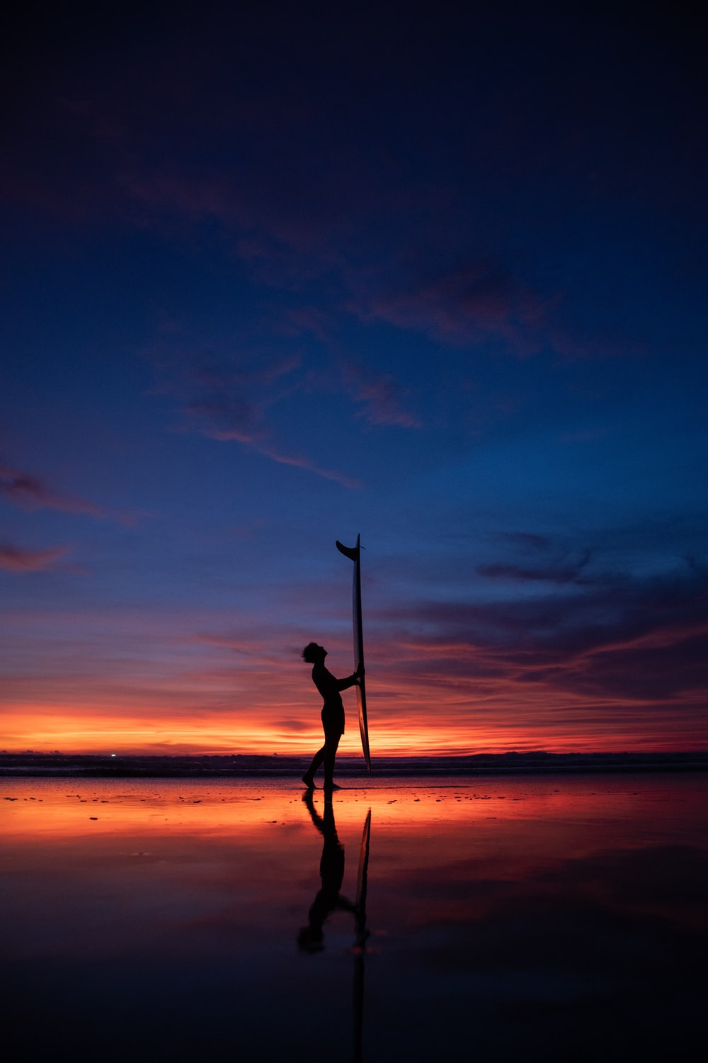 silhouette of man holding stick standing on seashore during sunset