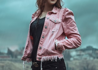 girl in pink denim jacket standing under white clouds during daytime