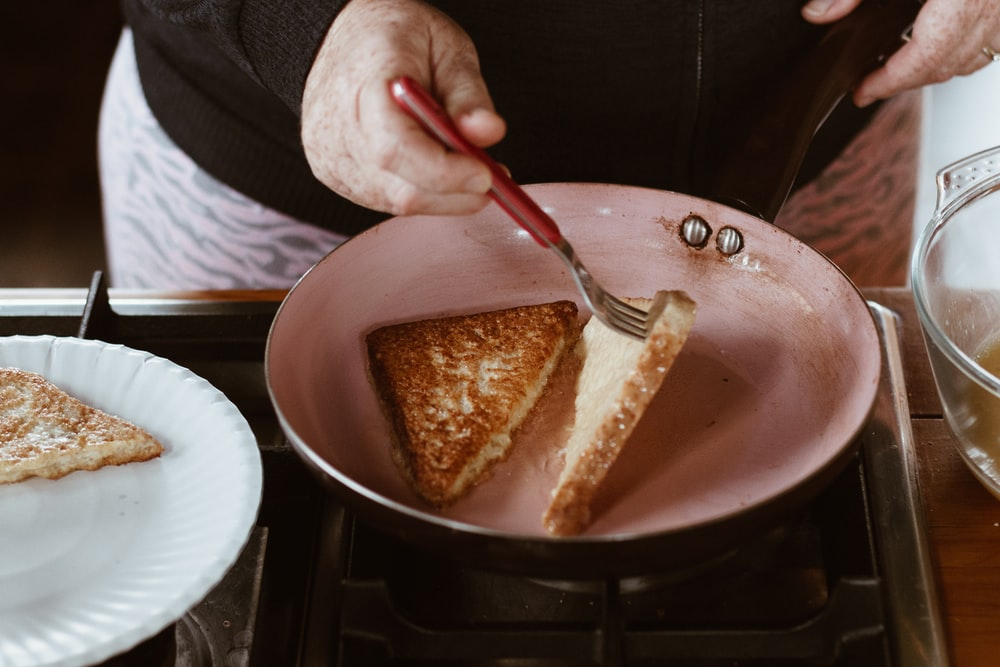person holding red handled knife slicing cake