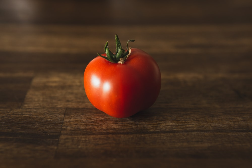 red tomato on brown wooden table