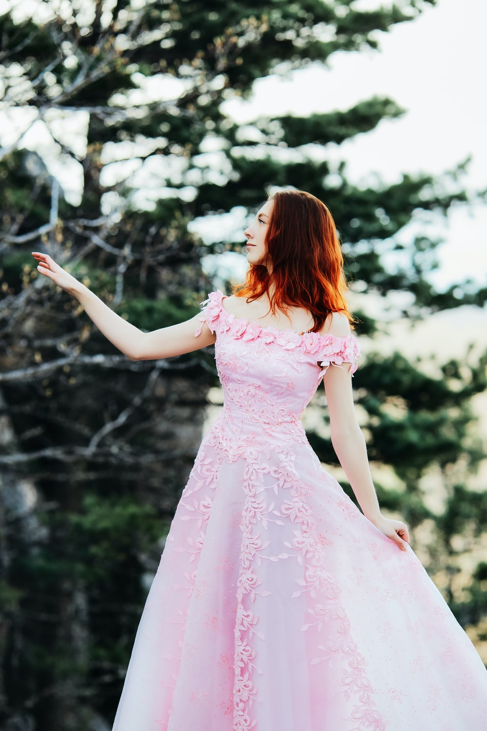 girl in pink dress standing on forest during daytime