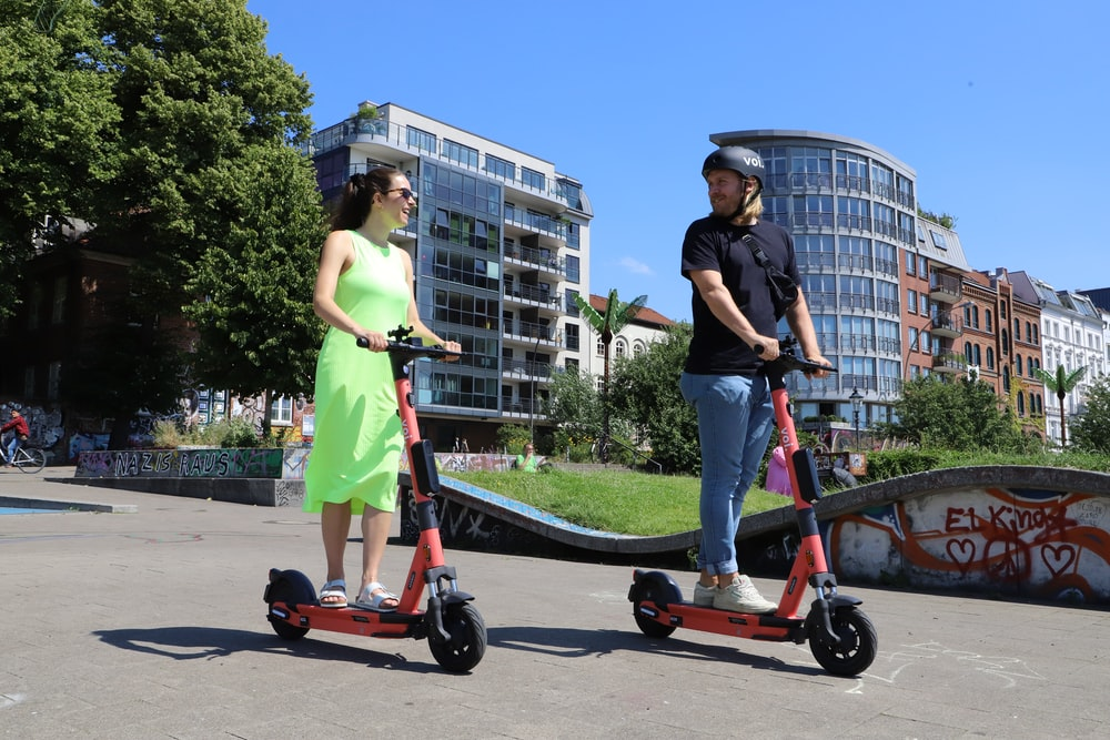 Woman and man are riding with portable electric scooters to save themselves from traffic jams